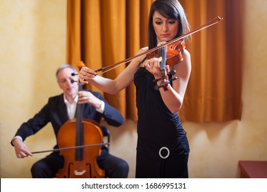 Woman playing her violin and a man playing cello