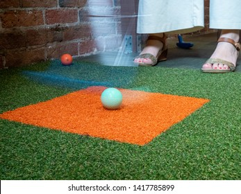 Woman playing miniature golf hitting a ball with a putter mid swing