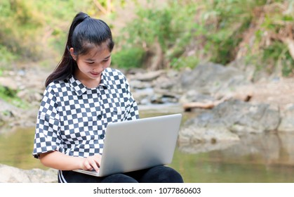 Woman Playing the notebook rock tree sunlight stream background