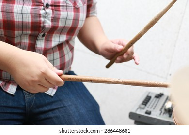 a woman playing on drum with drumsticks