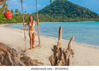 woman playing on a swing on a beach