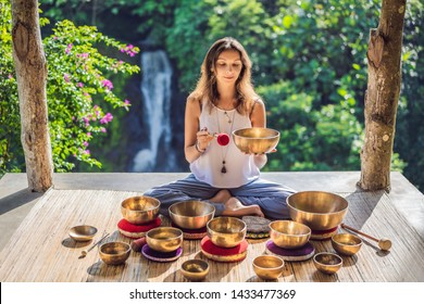 Woman playing on Tibetan singing bowl while sitting on yoga mat against a waterfall. Vintage toned. Beautiful girl with mala beads meditating