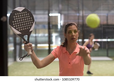 woman playing paddle tennis, ball bounce on glass