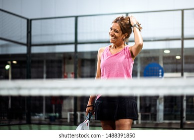 Woman playing padel in a green grass padel court indoor behind the net