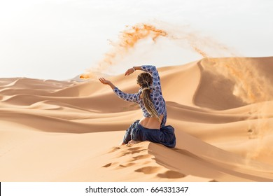 Woman playing with sand in the dunes of the Sahara desert.