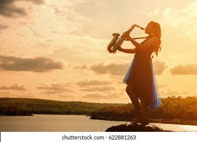 Woman playing saxophone sax at sunset