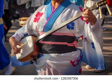 Woman playing shamisen on Awa Odori traditional japanese dance festival