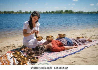 Woman playing a singing bowls also known as Tibetan Singing Bowls, Himalayan bowls. Making sound massage at beautiful sunny day.