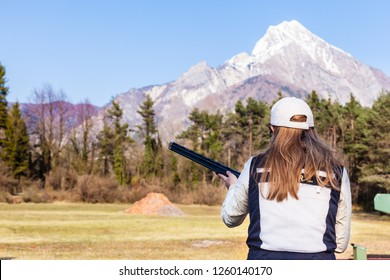 a woman playing skeet and aiming at the clay pigeons with a hunting rifle or shotgun on a sunny day
