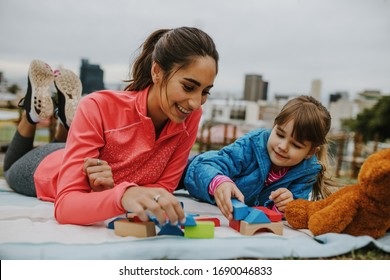 Woman playing with a small girl at the park. Girl child playing building blocks with her nanny at the park. Both lying on a plaid.
