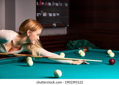 woman playing snooker, she is aiming to shoot the snooker ball, holding hands on snooker table. billiards