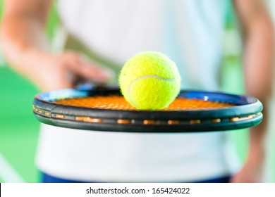 Woman playing tennis, only upper body with racket and ball, giving service