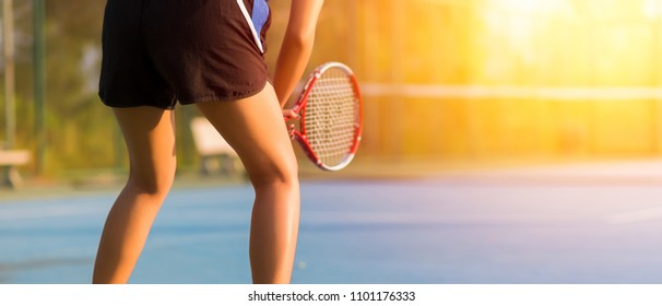 Woman playing tennis and waiting for the service. sunset banner panoramic crop for copy space.