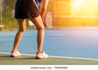 Woman playing tennis and waiting for the service. sunset