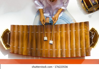 Woman playing a traditional wooden Thai musical instrument, ranat ek, resembling a xylophone is played with mallets seen from directly above