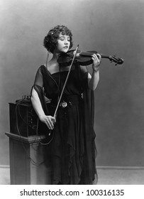 Woman playing violin with headphones
