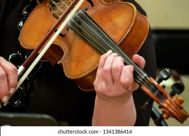 Woman playing the violin. Musical theme. Female fingers grip the strings and hold the bow. Close-up. Shallow depth of field. Selective focus.