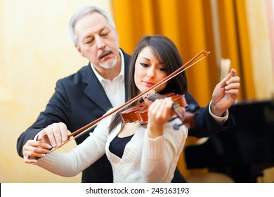 Woman playing the violin with a teacher