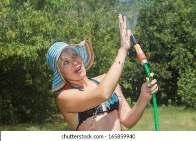 Woman playing with water hose on a sunny day
