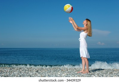 The woman plays with a ball at coast