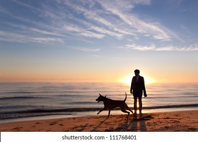 Woman plays with dog on the shore of the lake at sunrise
