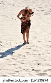 woman plays mandolin at the beach