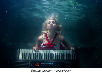 Woman plays the piano under water, she is a mermaid.