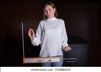 Woman plays the thereminvox - an electric musical instrument