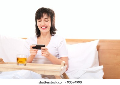 Woman plays video games on mobile smartphone in bed in bed isolated on white