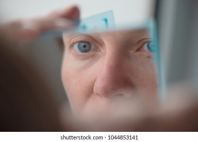 Woman plucking eyebrows with tweezers by the window, selective focus