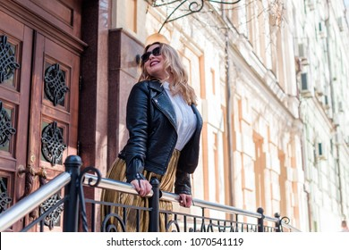 A woman of plus size, American or European appearance walks at city streets enjoying life. A young lady with excess weight, have a stylish dress. Natural beauty