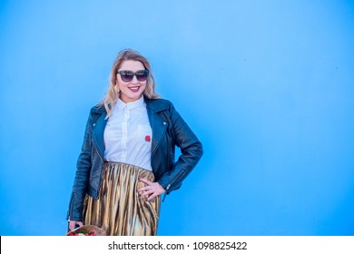 A woman of plus size, American or European appearance walks in the city enjoying life. A young lady with excess weight, xl size at the center of the city. Natural beauty