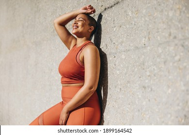 Woman with plus size body leaning to a wall and relaxing after workout session outdoors. Woman in sports clothing taking a break from exercise.