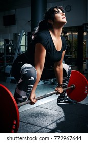 Woman plus size in gym doing exercises with barbell powerlift, female XXL losing weight, fat model working with her body in fitness hall, healthy lifestyle and diet
