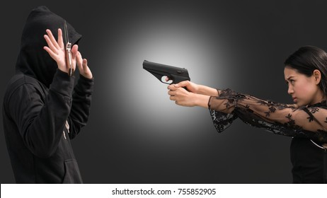 A woman point hand gun to the theft in black hood dress holding knife