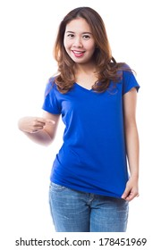 Woman pointing to blank blue t-shirt on white background