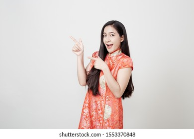 Woman pointing to blank space, Beautiful Asian woman wearing red Chinese traditional dress smiling  on gray banner background with copy space for concept Happy chinese new year