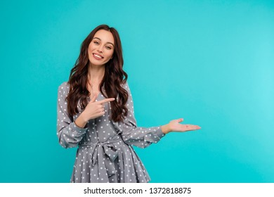 Woman pointing at copy space at palm of hand isolated over bright blue background