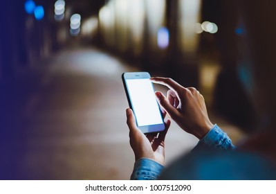 Woman pointing finger on blank screen smartphone on background bokeh light in night atmospheric city, hipster using clean gadget mobile phone closeup, mockup street, online wifi internet concept