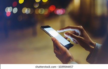 Woman pointing finger on blank screen smartphone on background bokeh light in night atmospheric city, blogger hipster using in hands gadget mobile phone, mockup street, online wifi internet concept