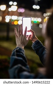 Woman pointing finger on blank screen smartphone on background bokeh light in night atmospheric city, hipster using in hands clean gadget mobile phone closeup, mockup street, online wif internet