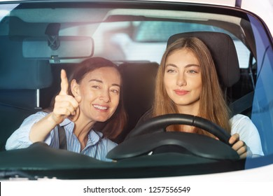 Woman pointing finger on something sitting in car