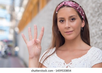 woman pointing up four fingers, number 4, forth, 4 important keys, counting concept