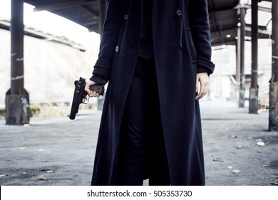 Woman pointing a gun. Woman stands with a pistol in his hand