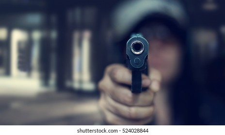Woman pointing a gun at the target on dark background, selective focus on front gun, vintage color tone