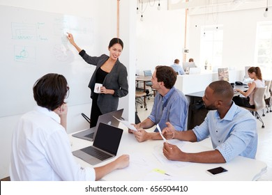 Woman pointing at whiteboard at a meeting in a busy office