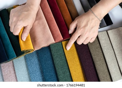 The woman points to the colored fabric that she likes, she chooses the fabric in the catalog with fabric samples for her new sofa. Flat lay