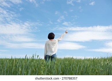 Woman poiting up to copyspace in green field