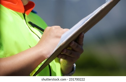 Woman police officer fills out the form for car driver