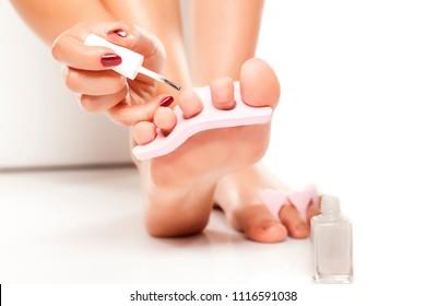 woman polishing her toenails with nail polish separator on white background